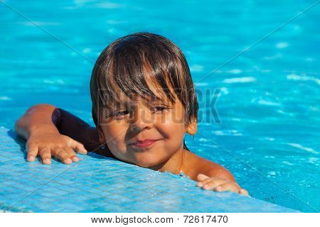 Smiling soppy boy looking happily in swimming pool