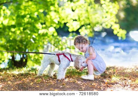 Adorable Little Baby Girl Playing With A Poodle Dog On A River Shore In A Park On A Sunny Summer Day