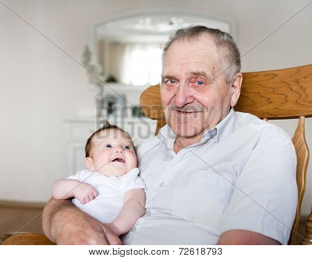 Portrait Of A Great Grandfather Holding A Newborn Baby Girl