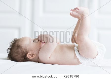 Funny Baby Girl Relaxing In A Diaper On A White Blanket With Er Legs And Feet Up In The Air