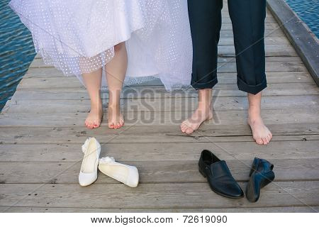 Wedding Couple's Feet Standing On The Wooden Bridge.