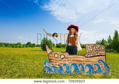 Pirate girl with black hat, sword stands on ship