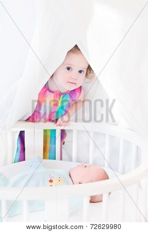 Funny Curly Toddler Girl Hiding From Her Newborn Baby Brother At A White Bed