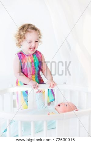 Adorable Laughing Toddler Girl Standing At A White Round Bed Of Her Cute Newborn Baby Brother