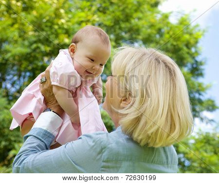 Grandmother Lifting Grandchild Up And Playing
