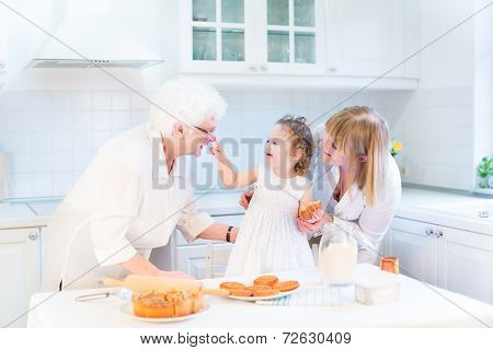 Funny Toddler Girl Playing In A Kitchen, Having Fun Baking An Apple Pie With Two Of Her Grandmothers