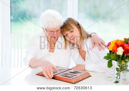 Beautiful Woman And Her Loving Mother Watching Together A Black And White Photo Album