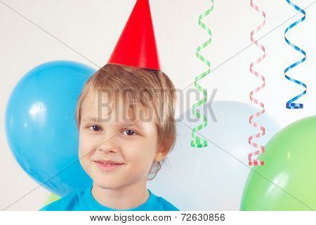 Little blonde boy in festive cap with holiday balls and streamer
