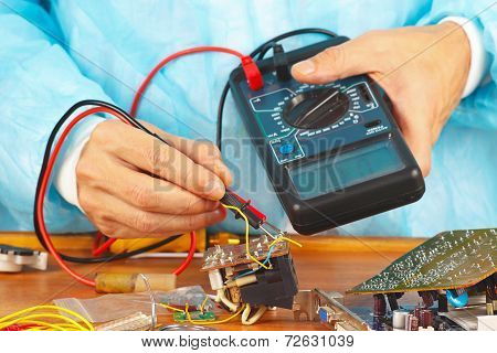 Serviceman checks electronic hardware with a multimeter in service workshop