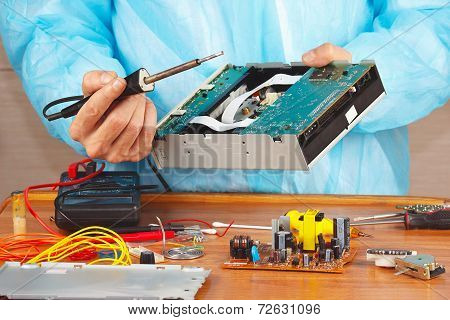 Repair electronic hardware with a soldering iron in service workshop