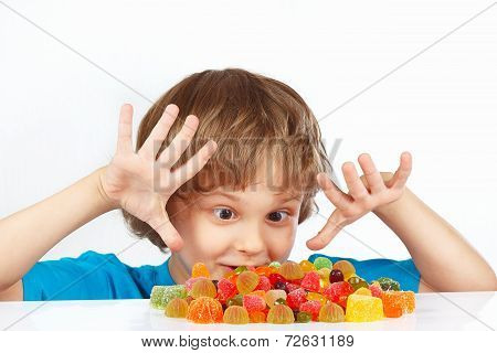 Little boy with colored jelly candies on white background