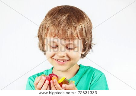 Boy with colored sweets and jelly candies on white background