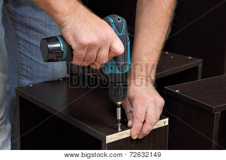 Hands Carpenter With Screwdriver, Tighten Screw In Drawers Of Chipboard.