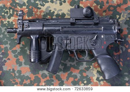 modern 9 mm submachine gun on camouflaged background