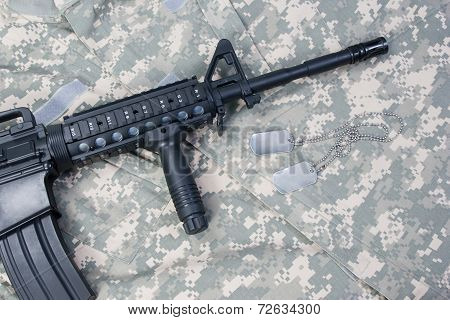 M4 Carbine With Blank Dog Tags On Camouflage Uniform