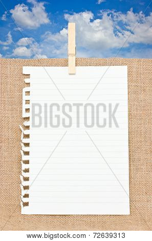 Ripped off paper with wooden clothespin on burlap in front of blue sky.