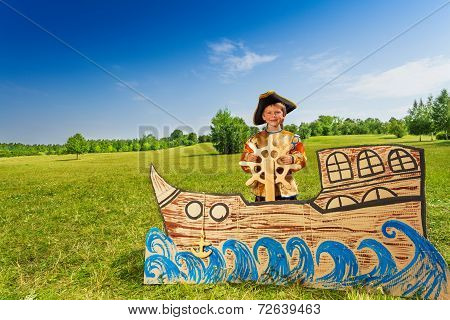 Happy boy in pirate costume holds helm of  ship
