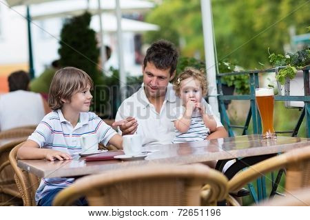 Young Father Relaxing In Outside Cafe With His Children having a drink together on nice warm summ