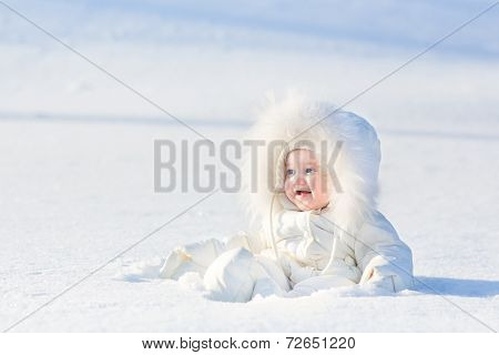 Adorable Laughing Baby Girl In A Warm White Snow Suit In Snow On Very Sunny  Winter Day In Park