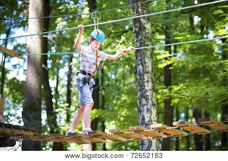 Cute School Boy Enjoying A Sunny Day In A Climbing Activity Park