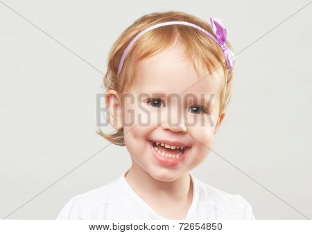 Beautiful Happy Little Girl Laughing And Smiling On A Gray Background