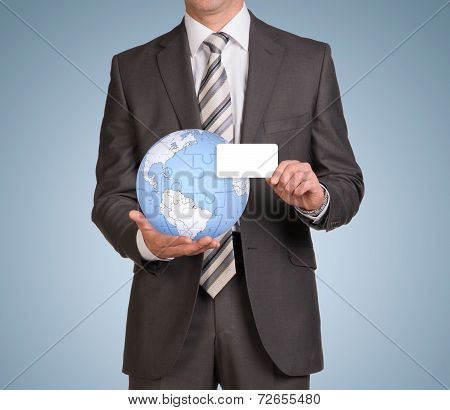 Man hold empty card and earth globe consisting of puzzles