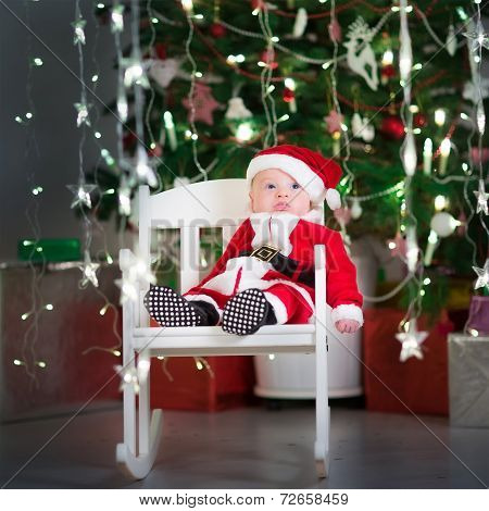 Cute Newborn Baby In A Santa Costume And Hat Sitting In A White Rocking Chair Under A Christmas Tree