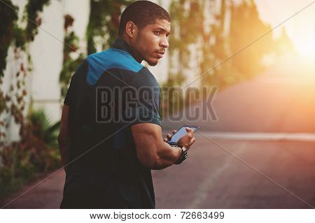 Male sportsman walking on the road to sunset holding phone in the hands
