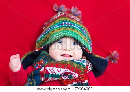 Funny Baby Girl In A Colorful Knitted Hat And Scarf On A Red Blanket
