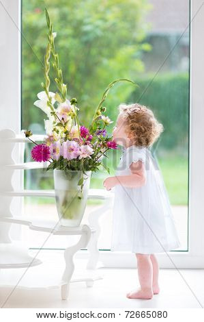 Adorable baby girl with curly hair wearing a white dress smelling beautiful flowers