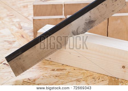 Hand Saw Cutting Through A Beam Of Wood