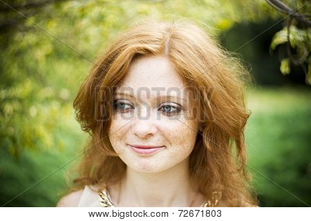 Portrait Of Redhead Girl With Blue Eyes On Nature