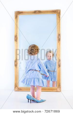 Little Toddler Girl With Beautiful Curly Hair Wearing A Blue Dress Standing In Front Of A Big Mirror