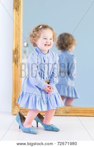 Funny Laughing Toddler Girl With Curly Hair Wearing A Blue Dress Is Trying On Her Mother's Shoes