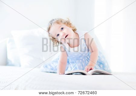 Beautiful Little Toddler Girl With Curly Hair In A Blue Dress Reading A Book At A White Bed
