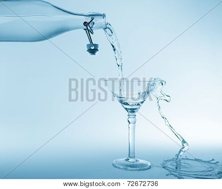 Clear Water Pour Out Of Bottle Splash Into Glass And Spill With Blue Back Lighting