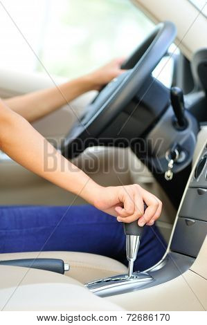 woman driver shifting the gear stick and driving a car