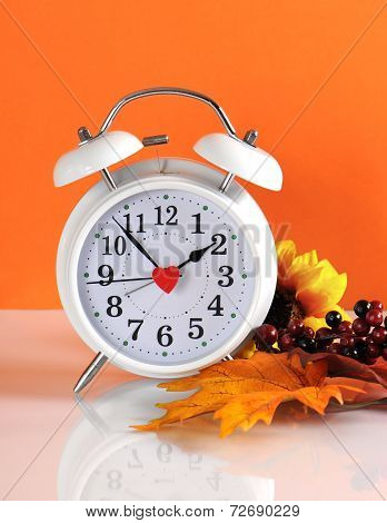 Daylight Savings Time Ends In Autumn Fall With Clock Concept On Orange Background.