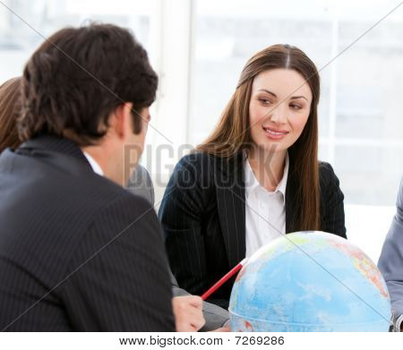 Confident Businessteam Looking At A Terrestrial Globe