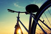 stock photo of color wheel  - Beautiful close up scene of bicycle at sunset sun on blue sky with vintage colors silhouette of bike forward to sun wonderful rural of Mekong Delta Vietnam countryside - JPG