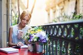 image of morning  - Pretty young woman reading book while sit at terrace table on her balcony - JPG