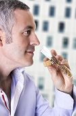 stock photo of mullet  - A man samples the smell of a mullete of cologne or perfume - JPG