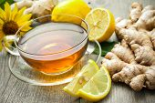 stock photo of rhizomes  - Cup of ginger tea with lemon on wooden table - JPG