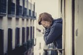 pic of suffering  - young attractive woman suffering depression and crying in stress outdoors at home balcony terrace window - JPG