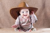 stock photo of baby cowboy  - Happy laughing baby wearing a cow girl outfit with a big hat - JPG