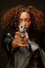 image of gangsta  - A young beautiful african american female holds a semi automatic pistol during this dark photo shoot against black - JPG