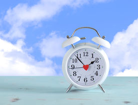 foto of time-saving  - Daylight savings time white clock on a vintage aqua blue wood table against a sky with clouds background - JPG