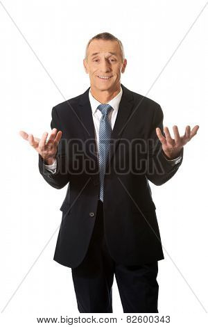 Mature businessman in undecided gesture.