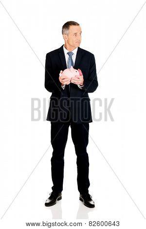 Full length confused businessman holding piggybank.