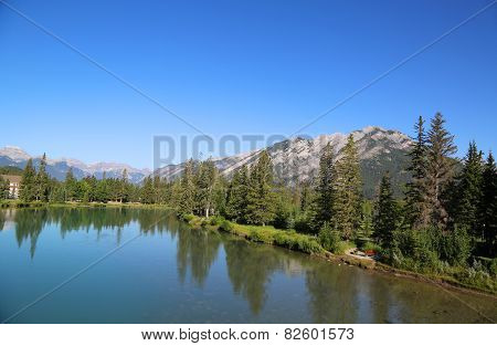 Reflection in Bow River near City of Banff in Alberta, Canada